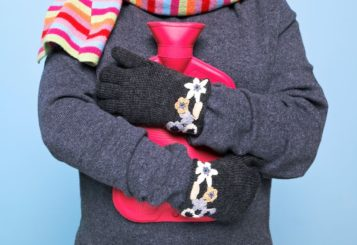 photo-of-a-woman-holding-a-red-hot-water-bottle-to-her-chest-whilst-wearing-hand-kniited-woolen-glov